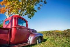 Старая красная тележка фермы припарковала под деревом осени Стоковая Фотография RF