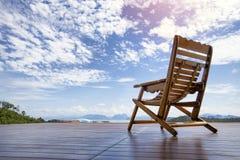 Старая кресло-качалка древесиной на деревянном поле перед стулом Seascape стоковые фотографии rf