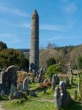 Старая круглая башня в кладбище на историческом месте Glendalough монашеском в графстве Wicklow в Ирландии Стоковое Изображение RF