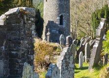 Старая круглая башня в кладбище на историческом месте Glendalough монашеском в графстве Wicklow в Ирландии Стоковые Фотографии RF