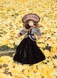 Старая кукла фарфора на предпосылке разрешения гинкго Стоковая Фотография