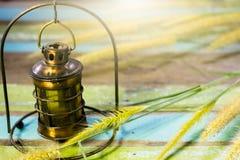Старая лампа на таблице с травой цветет Стоковое фото RF