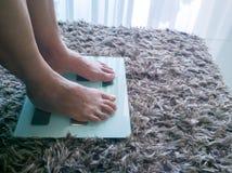 Старая мать на устрашении для того чтобы измерить потерю веса Стоковое Изображение