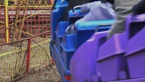 Старая миниатюрная езда американской горкы вверх по рельсу Красочные будочки с людьми принимают повороты акции видеоматериалы
