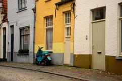 Старая мощенная булыжником улица, желтая стена и зеленый самокат стоковые изображения