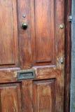 Старая, нанесенная шрам деревянная дверь дома, с латунным шлицем письма Стоковое Фото