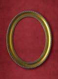 Старая овальная золотая рамка на красной стене Стоковое фото RF