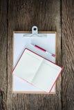 Старая доска сзажимом для бумаги, красная тетрадь, красная ручка на grungy деревянной поверхности Стоковая Фотография RF