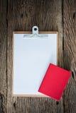 Старая доска сзажимом для бумаги, красная тетрадь на grungy деревянной поверхности Стоковые Фотографии RF