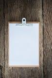 Старая доска сзажимом для бумаги на grungy деревянной поверхности Стоковые Изображения