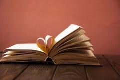 Старая открытая книга hardback, страница украшает в форму сердца для влюбленности в ` s валентинки влюбленность с открытым сердце Стоковое Изображение RF