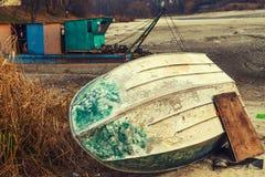 Старая переворачиванная синь шлюпки лежит на береге высушенного озера Стоковые Изображения RF