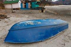 Старая переворачиванная синь шлюпки лежит на береге высушенного озера Стоковое фото RF