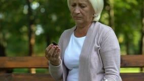 Старая плача женщина смотря кольцо и отжимая его к комоду, памятям, боли потери сток-видео