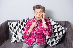 Старая пожилая бабушка женщины с серыми волосами сидит дома на кресле  стоковые изображения