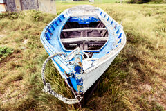 Старая покинутая деревянная рыбацкая лодка, который сели на мель на земле и траве Стоковые Изображения RF