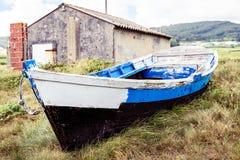 Старая покинутая деревянная рыбацкая лодка, который сели на мель на земле и траве Стоковые Фото