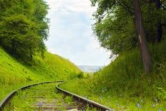 Старая покинутая железная дорога среди заросших лесом холмов Стоковые Изображения RF