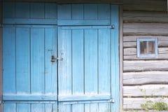 Старая покрашенная голубая деревянная дверь к старому амбару Голубая деревянная дверь w Стоковое Фото