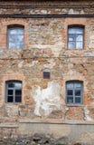 Старая померанцовая кирпичная стена с 4 окнами Стоковое Изображение RF