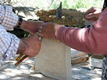 Старая португальская пара создавая программу-оболочку кожа овец вокруг традиционного барабанчика стоковые фото