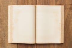 Старая пустая книга открытая на деревянной таблице Стоковые Фотографии RF