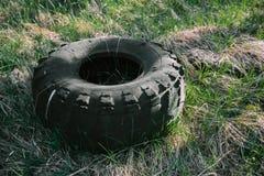 Старая резина автошины тележки лежа на траве стоковая фотография