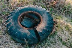 Старая резина автошины тележки лежа на траве стоковые фото