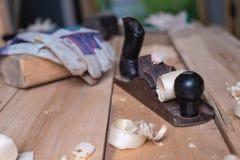 Старая ретро рука более плоская с перчатками и мушкелом на деревянном столе с опилк и shavings плотничество, деревянный толь, дер стоковая фотография