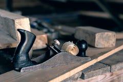Старая ретро рука более плоская с перчатками и мушкелом на деревянном столе с опилк и shavings плотничество, деревянный толь, дер стоковое изображение rf