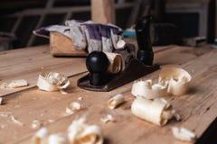 Старая ретро рука более плоская с перчатками и мушкелом на деревянном столе с опилк и shavings плотничество, деревянный толь, дер стоковая фотография rf