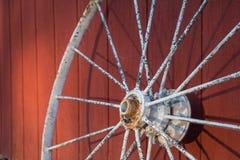 Старая ржавая белая склонность колеса телеги против красного амбара Стоковое фото RF