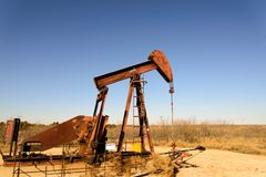 Старая ржавая нефтяная вышка в солнечном свете с голубым небом Стоковая Фотография RF