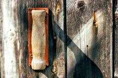 Старая ржавая сломанная ручка двери на деревянной двери старого амбара тонизировано Стоковое Фото