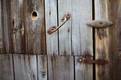 Старая ржавая смертная казнь через повешение замка на серой деревянной двери Стоковое Изображение