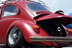 Старая ржавая часть задней части автомобиля VW Volkswagen красного цвета восстановила колеса показанные в общественном месте для  Стоковые Изображения RF