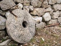 Старая склонность жернова против каменной стены Стоковая Фотография RF