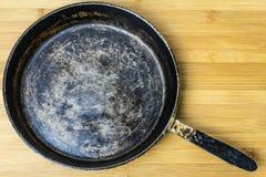Старая сковорода на бамбуковой предпосылке Фото старого лотка Стоковые Фото