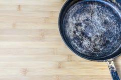 Старая сковорода на бамбуковой предпосылке Фото старого лотка Стоковая Фотография RF
