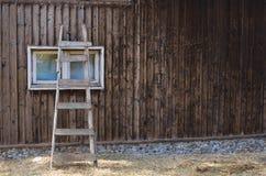 Старая склонность лестницы против деревянных дома и окна Стоковые Изображения