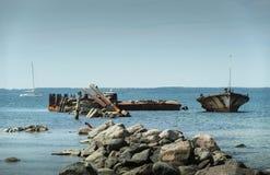 Старая сломанная развалина шлюпки на береге, голубом море и паруснике на предпосылке Стоковые Фото