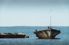 Старая сломанная развалина шлюпки на береге, голубом море и паруснике на предпосылке Стоковое Фото