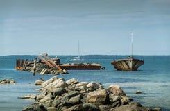 Старая сломанная развалина шлюпки на береге, голубом море и паруснике на предпосылке Стоковая Фотография
