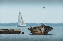 Старая сломанная развалина шлюпки на береге, голубом море и паруснике на предпосылке Стоковая Фотография RF