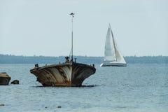 Старая сломанная развалина шлюпки на береге, голубом море и паруснике на предпосылке Стоковое Изображение