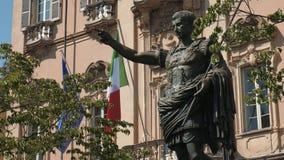 Старая статуя императора Augustus перед итальянским и европейским флагом в Павии, Италии видеоматериал