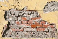 Старая стена желтого цвета шелушения Обрушенные гипсолит и кирпичная кладка Предпосылка и текстура Стоковая Фотография