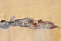 Старая стена желтого цвета шелушения Обрушенные гипсолит и кирпичная кладка Предпосылка и текстура Стоковое фото RF