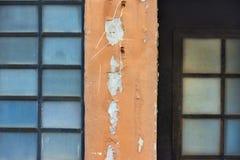 Старая стена с квадратами окон металл-пластмассы с синим стеклом, в середине часть стены с оранжевым гипсолитом Стоковое Изображение RF