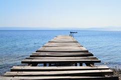 Старая сломанная деревянная пристань в спокойном голубом море Стоковая Фотография RF